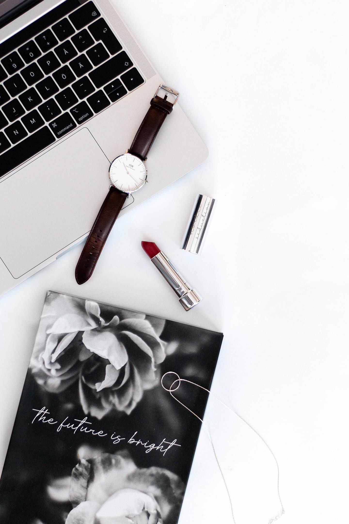 2019 lifestyle flatlay with MacBook, DW watch and lipstick.
